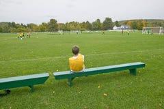 En pojke vilar på en bänk under skolafotbollövning, New Hampshire Royaltyfri Bild