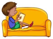 En pojkeläsning, medan sitta ner Arkivbild