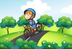 En pojkeridning i hans cykel Arkivfoton