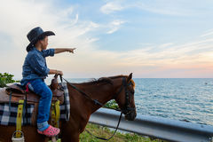 En pojkeridninghäst med handatt peka och blick ut till havet Fotografering för Bildbyråer