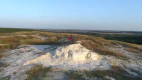 En pojkeuppklädd med en udde av stålmananseendet på ett berg som ser solnedgången lager videofilmer