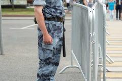 En polis med en taktpinne nära metallstaketet, närbild arkivfoto