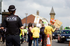 En polis Overlooking anti--Frackingprotesten i Preston Royaltyfri Foto