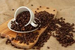 En porslinkopp och kaffebönor Arkivbild