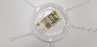 En porslinpengarsedel på den tomma vita plast- plattan royaltyfria foton