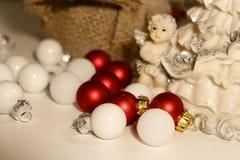 En porslinstatyett som omges av mycket små julstruntsaker i rött och vitt royaltyfria foton