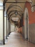 En portik i bolognaen, Italien En lampa som hänger från det välvda taket arkivfoton