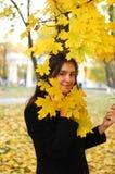En portret av den lyckliga unga attraktiva flickan i en höst parkerar Gladlynta sinnesrörelser, höstlynne Arkivbild