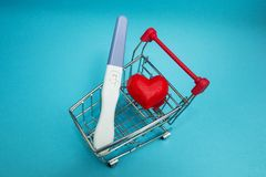 En positiv graviditetstest och en röd hjärta i en shoppa vagn royaltyfri foto