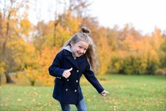 En positiv ljus höststående av en gullig le liten flicka arkivfoto