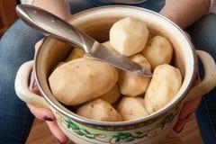 En potatis skalas med en kökkniv Arkivfoton