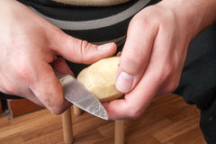 En potatis skalas med en kökkniv Royaltyfria Bilder
