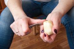 En potatis skalas med en kökkniv Royaltyfri Foto
