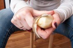 En potatis skalas med en kökkniv Fotografering för Bildbyråer