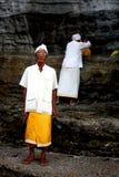 En präst och hans assistent i Bali, Indonesien Royaltyfria Bilder
