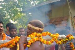 En präst som kommer med det heliga vattnet för dyrkanen av Lord Shiva byinvånarna tycker om programet arkivbilder