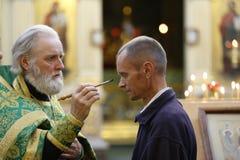 En präst suddar en panna för man` s med heligt vatten Arkivbilder