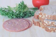 En préparant le blé entier panez et jambon pour faire le sandwich photographie stock