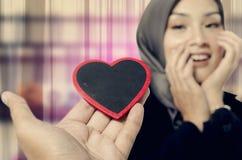 En présentant le symbole et l'amie d'amour choquez l'expression tandis que regard à lui Image libre de droits