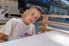 En preteenpojke i vitt t-skjorta sammanträde av tabellen och innehavet en flaska av vatten i shoppinggalleria royaltyfri fotografi