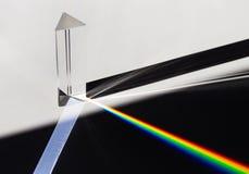 En prisma som skingrar solljus som delar in i ett spektrum på en vit bakgrund royaltyfri bild