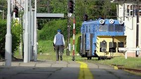 En pro-man i likformig går vidare en järnväg i sommar i slo-mo stock video
