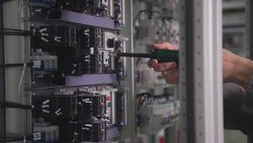 En professionell monterar en elektrisk strömkrets och vrider en skruvmejsel stock video