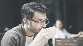 En profil av den stiliga mannen i glasögon som dricker kaffe royaltyfria bilder