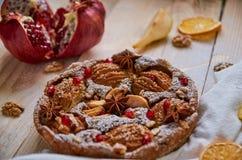 En pudrad päronpaj som dekoreras med den vita torkduken, nya skivade päron och granatäpplet, torkade apelsiner, valnötter, anisst Fotografering för Bildbyråer