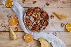 En pudrad päronpaj som dekoreras med den vita torkduken, nya skivade päron, torkade apelsiner, valnötter, anisstjärnor, sked Royaltyfri Bild