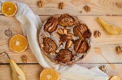 En pudrad päronpaj som dekoreras med den vita torkduken, nya skivade päron, torkade apelsiner, valnötter, anisstjärnor, sked på t Royaltyfri Foto