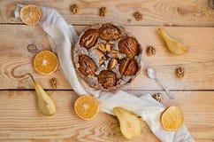En pudrad päronpaj som dekoreras med den vita torkduken, nya skivade päron, den torkade valnöt- och silverskeden för apelsiner, p Arkivbild