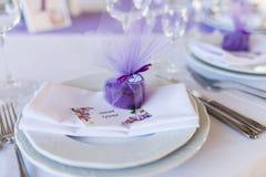 En purpurfärgad bonbonniere för bröllop i en form av hjärta som ligger på en vit platta Royaltyfri Bild