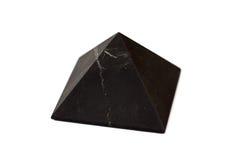 En pyramid av shungite som isoleras på vit bakgrund Arkivbild