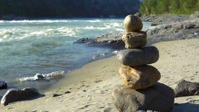 En pyramid av stenar står på flodbanken lager videofilmer
