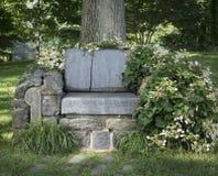 En rå stenbänk med att omge för blommor och för växter royaltyfri bild