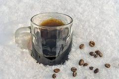 En råna av svart kaffe står i snön, spridda bönor royaltyfri bild