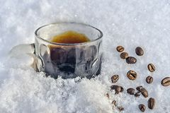 En råna av svart kaffe står i snön, spridda bönor arkivfoton