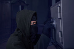 En rånare som försöker att öppna en säkerhetsask Royaltyfri Foto