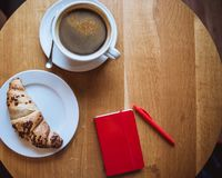 En röd anmärkning och en röd penna är på tabellen i ett kafé, en kopp kaffe och en giffel arkivbilder
