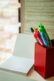 En röd ask av pennor är bredvid vitt tomt papper Royaltyfri Fotografi