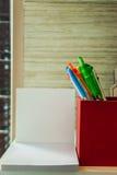 En röd ask av pennor är bredvid vitt tomt papper Arkivbild