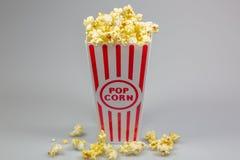 En röd avriven liten hink för popcorn som flödar över med popcorn arkivbilder