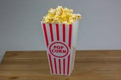 En röd avriven liten hink för popcorn som flödar över med popcorn fotografering för bildbyråer