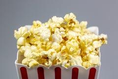 En röd avriven liten hink för popcorn som flödar över med popcorn arkivfoto