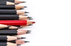 En röd blyertspenna mot den svarta blyertspennan Arkivfoto
