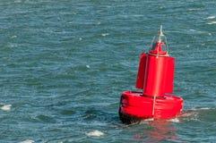 En röd boj som svävar på vatten Fotografering för Bildbyråer