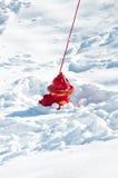 Röd brandpost som sjunkas i snow Arkivbild