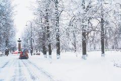 En röd bulldozer gör ren gatorna efter tungt naturligt snöfall jul som får klar frysa för dag arkivbild