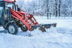 En röd bulldozer gör ren gatorna efter tungt naturligt snöfall jul som får klar frysa för dag royaltyfria foton
